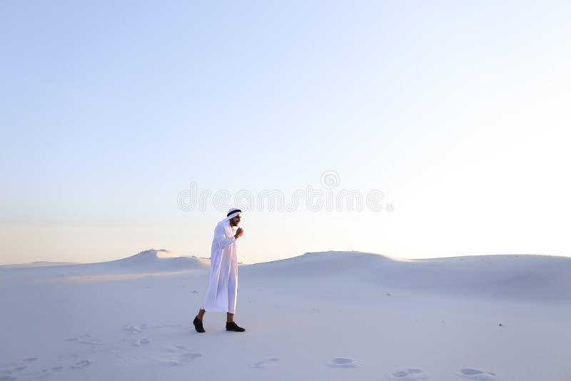 Den säkra grabben, arab går i mitt av den vita öknen och tycker om l arkivbilder
