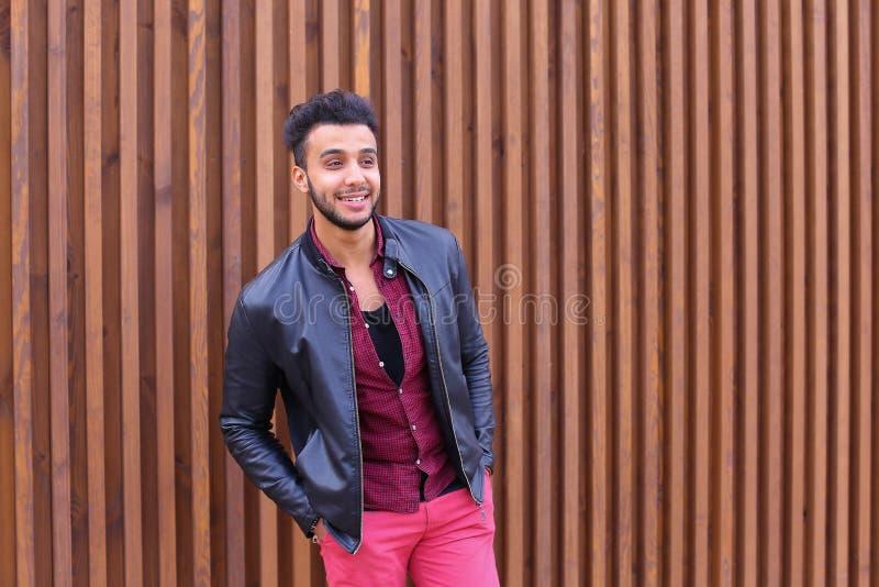 Den säkra gulliga unga muslimska mannen poserar och ser kameran, leende arkivbild