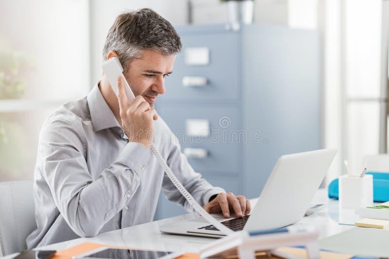 Den säkra le affärsmannen och konsulenten som arbetar i hans kontor, har han en påringning: kommunikation och affärsidé royaltyfri foto