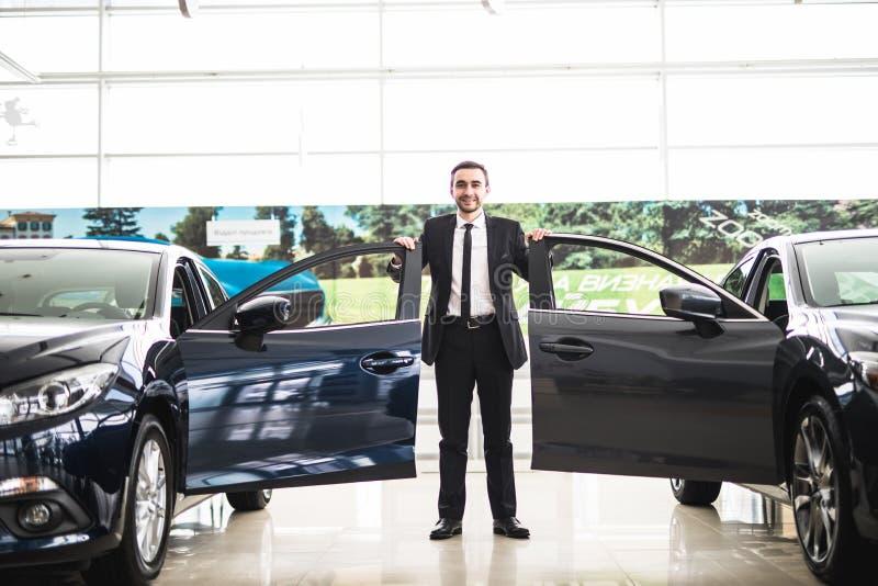 Den säkra le bilförsäljaren på visningslokalen nära två bilar, är han stående near öppna bildörrar av lyxiga bilar royaltyfri bild