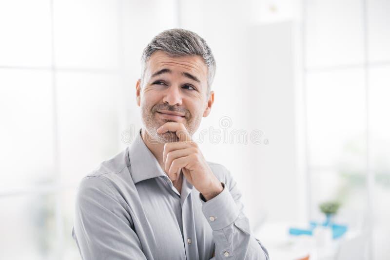 Den säkra le mannen som poserar och ler på kameran, tänker han med handen på hakan arkivfoton