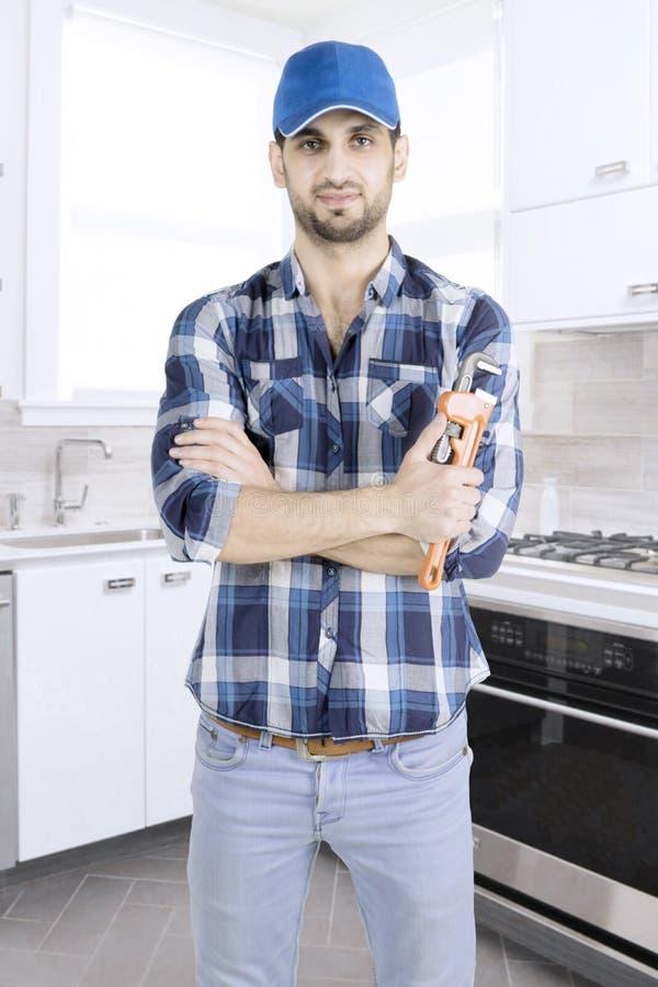 Den säkra rörmokaren står i köket arkivbilder