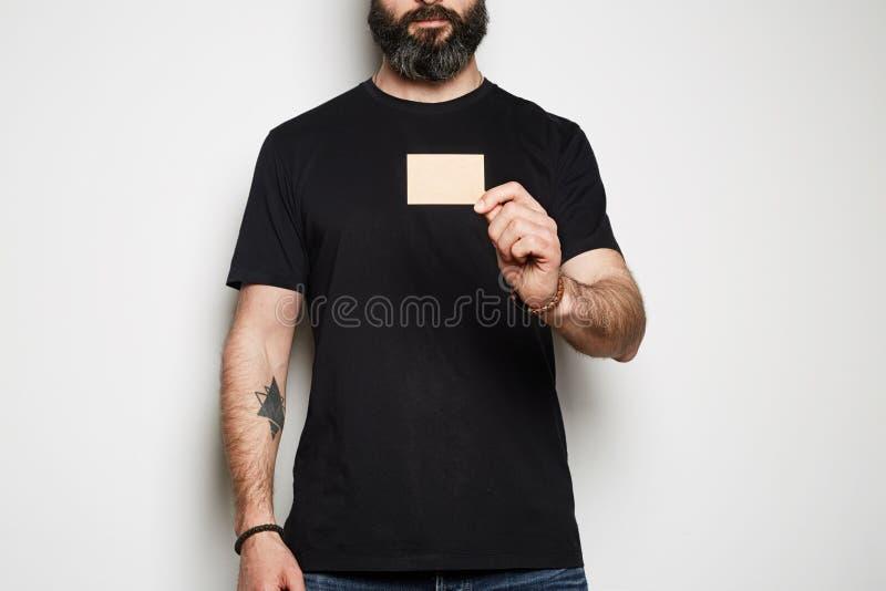 Den säkra skäggiga hipstermodellen poserar, i tillfällig tom svart t-skjorta högvärdig sommarbomull och att rymma det tomma  arkivfoto