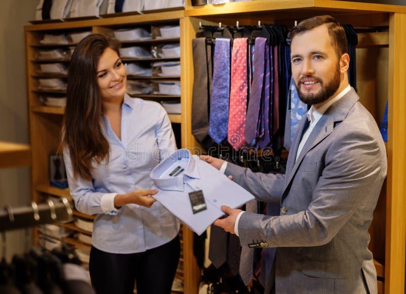 Den säkra stiliga mannen med skägget som väljer en skjorta i en dräkt, shoppar arkivfoton