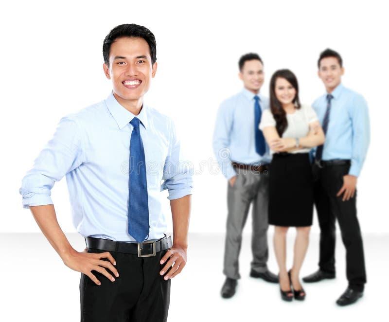 Den säkra unga affärsmannen och affären team som bakgrund arkivfoton
