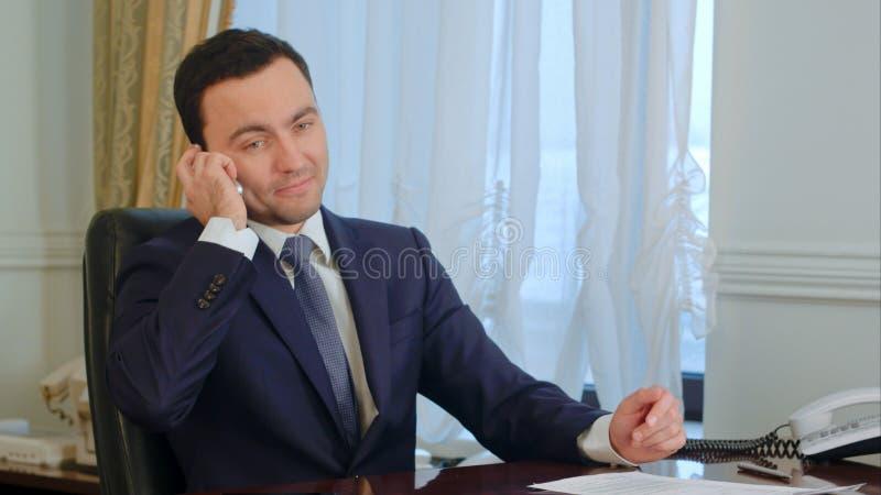 Den säkra unga affärsmannen tar en appell i ett modernt kontor royaltyfria foton