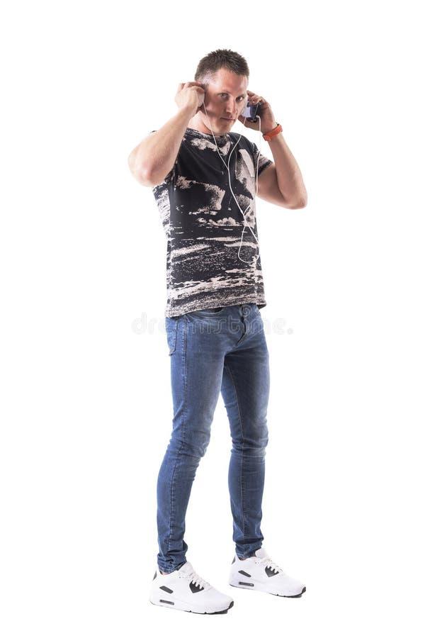 Den säkra unga mannen satte hörlurar på öron förbindelse till en mobiltelefon royaltyfri fotografi