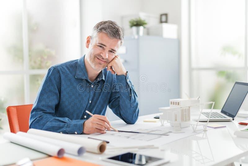 Den säkra yrkesmässiga arkitekten som poserar i hans kontor och ler på kameran, sitter arbetar han på skrivbordet och på en byggn arkivfoto