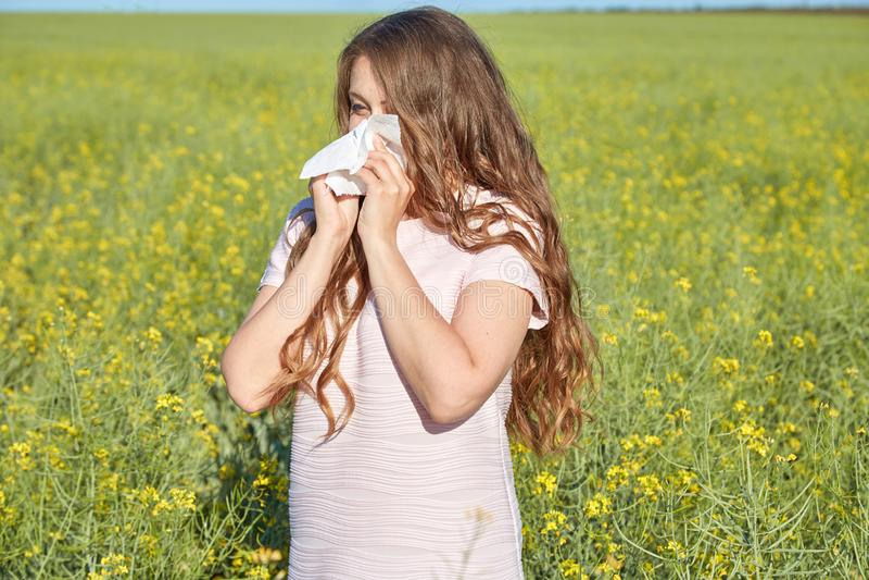 Den säsongsbetonade allergin till pollen, flickan nyser och stänger hennes näsa med en servett royaltyfri fotografi