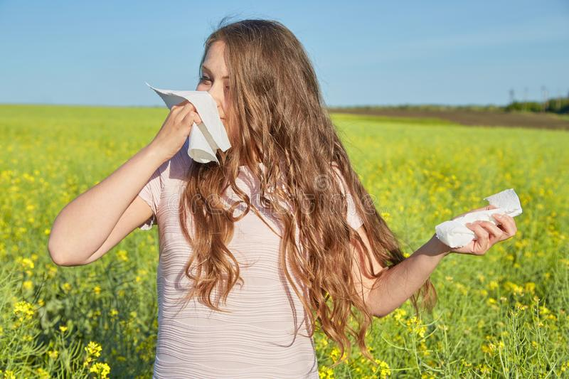 Den säsongsbetonade allergin till pollen, flickan nyser och stänger hennes näsa med en servett arkivfoto