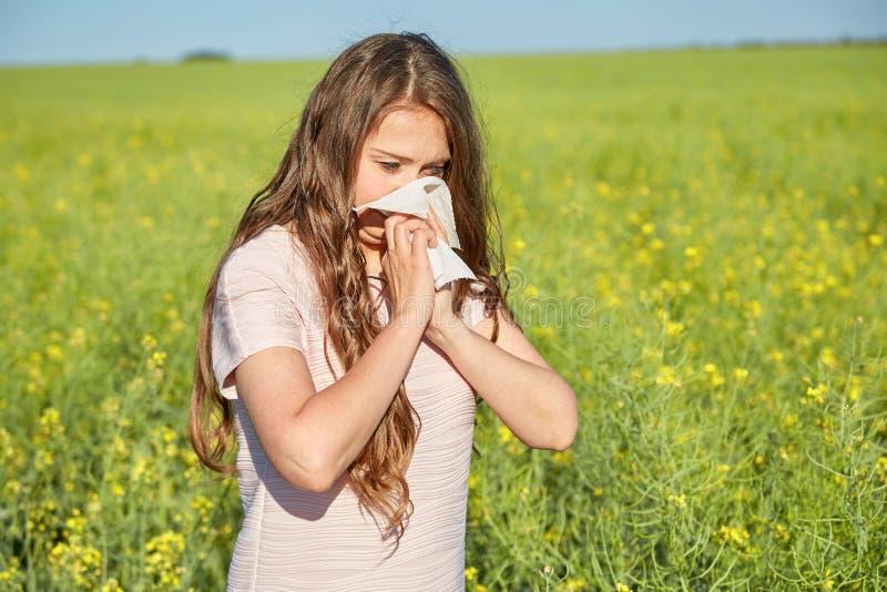 Den säsongsbetonade allergin till pollen, flickan nyser och stänger hennes näsa med en servett arkivbild
