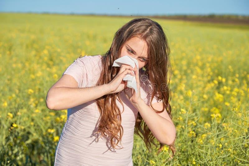 Den säsongsbetonade allergin till pollen, flickan nyser och stänger hennes näsa med en servett royaltyfri bild