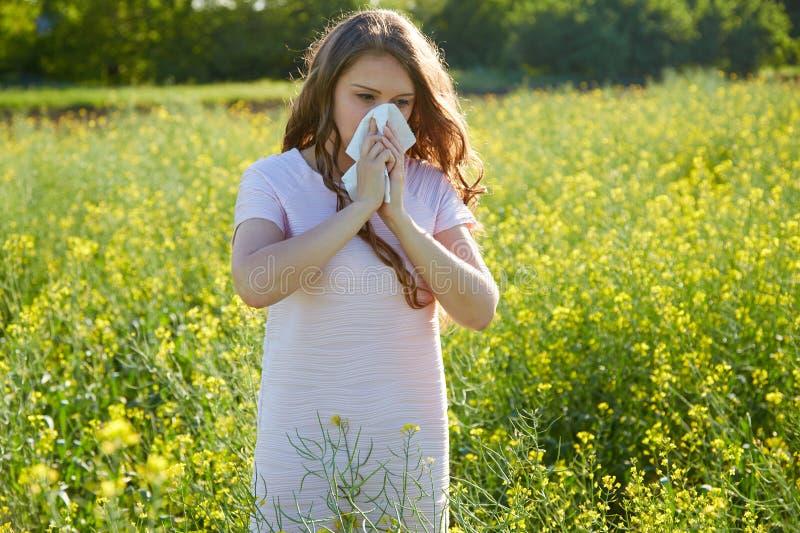 Den säsongsbetonade allergin till pollen, flickan nyser och stänger hennes näsa med en servett fotografering för bildbyråer