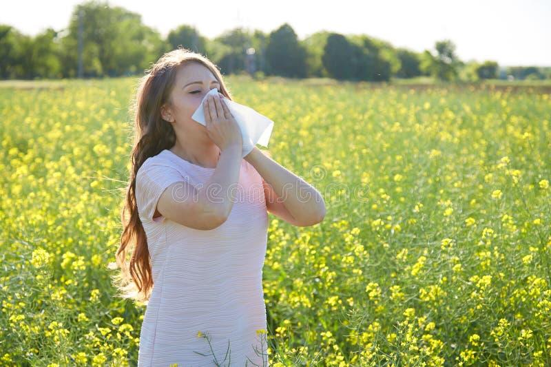 Den säsongsbetonade allergin till pollen, flickan nyser och stänger hennes näsa med en servett arkivbilder