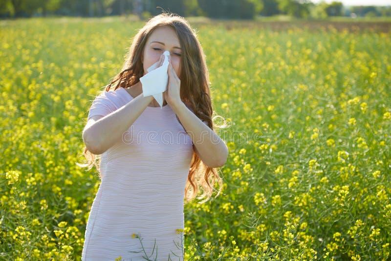 Den säsongsbetonade allergin till pollen, flickan nyser och stänger hennes näsa med en servett royaltyfria foton