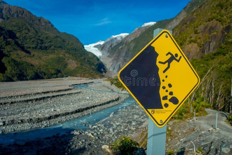 DEN SÖDRA ÖN, NYA SJÄLLAND MAY 25, 2017: Ett gult tecken av haverifara i ett härligt landskap av Franz Josef Glacier royaltyfri fotografi