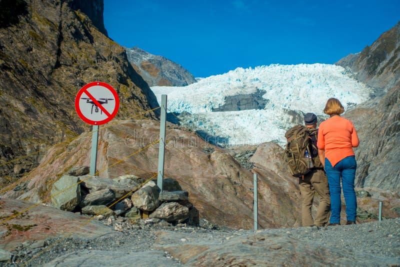 DEN SÖDRA ÖN, NYA SJÄLLAND MAY 23, 2017: Oidentifierade par som enoying sikten av Franz Josef Glacier och dalen royaltyfria bilder