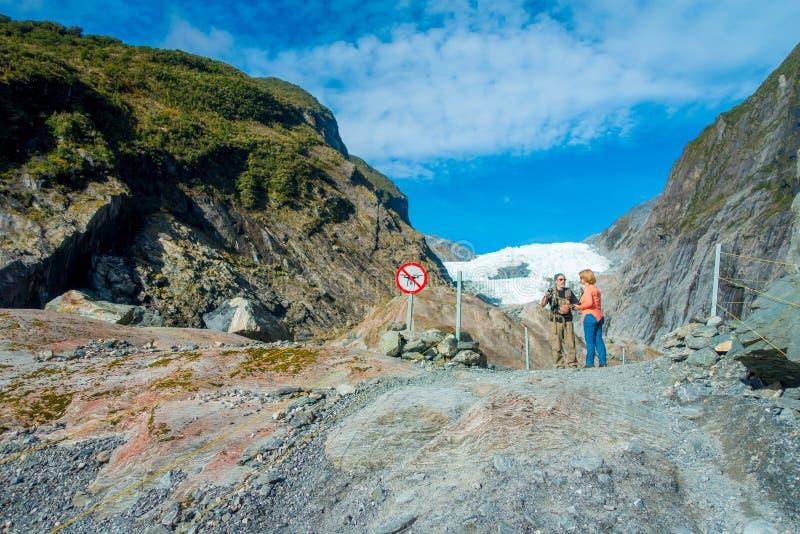 DEN SÖDRA ÖN, NYA SJÄLLAND MAY 23, 2017: Oidentifierade par som enoying sikten av Franz Josef Glacier och dalen arkivbild