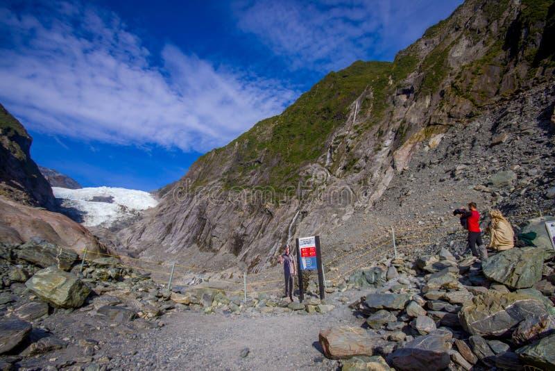 DEN SÖDRA ÖN, NYA SJÄLLAND MAY 25, 2017: Oidentifierat folk som fotvandrar det Franz Josef Glacier och dalgolvet, Westland royaltyfri fotografi
