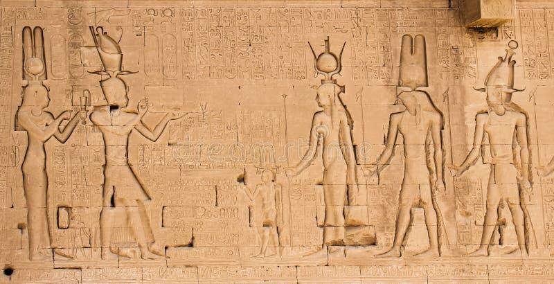 Den södra väggen av templet av Hathor på Dendera med lejon-hövdade skydrag Cleopatra och hennes sonkejsarsnitt på vänstra sidan royaltyfri foto