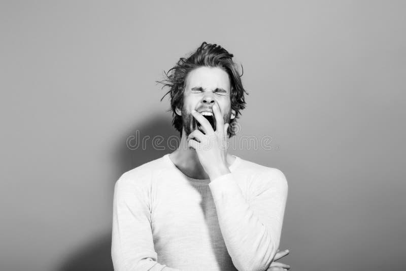 den sömniga gäspa mannen med långt uncombed hår, morgon vaknar upp arkivbild