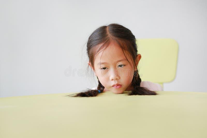 Den sömniga lilla asiatiska barnflickan satte huvudet på tabellen i klassrum mot vit bakgrund Trött skolflicka på skrivbordet arkivfoto