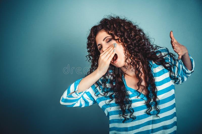 Den sömniga unga kvinnan med den breda öppna munnen som gäspar ögon, stängde blick royaltyfri bild