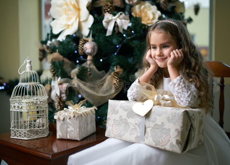 Den söta flickan tänkte sammanträde med gåvan nära julgranen royaltyfria foton