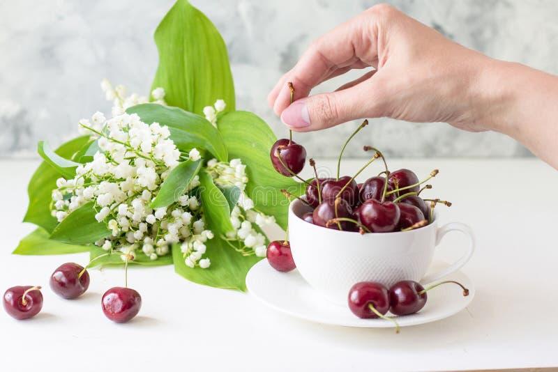 Den söta körsbäret i en vit rånar och en bukett av liljekonvaljer på en vit tabell Den kvinnliga handen tar den söta körsbäret arkivbilder