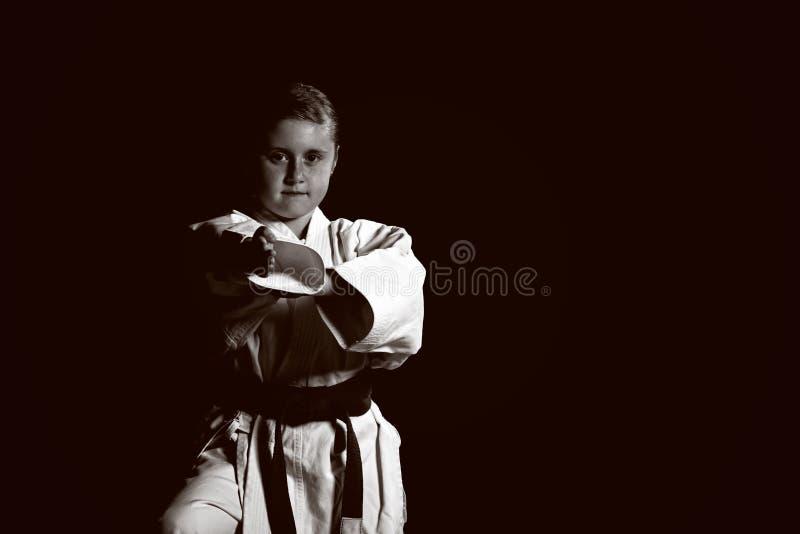Den söta lilla flickan i kampsporter övar som karateungen bara som isoleras på svart bakgrund royaltyfria bilder