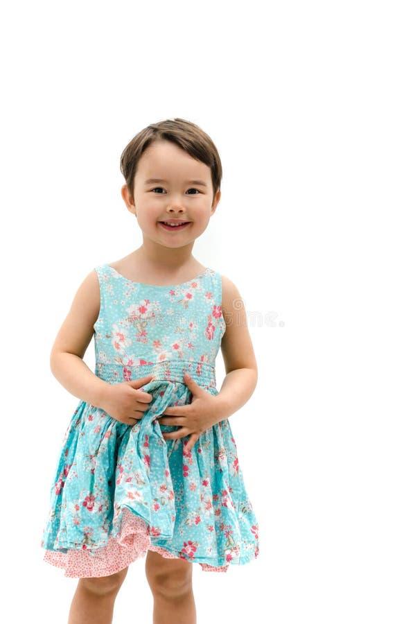 Den söta lilla flickan som ler i härliga blått, klär isolerat på wh royaltyfria bilder