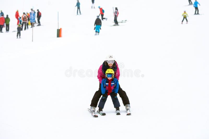 Den söta unga pojken och hans modern som lär att skida på ett milt, skidar sl royaltyfri foto