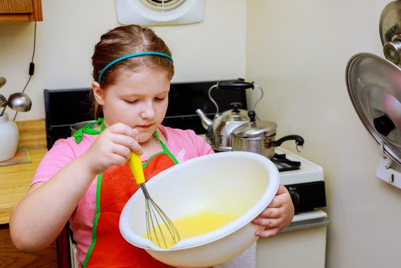 Den sött lite gulliga flickan lär hur man gör en kaka, i de hem- kitchenlearnsna för att laga mat ett mål i köket arkivbild