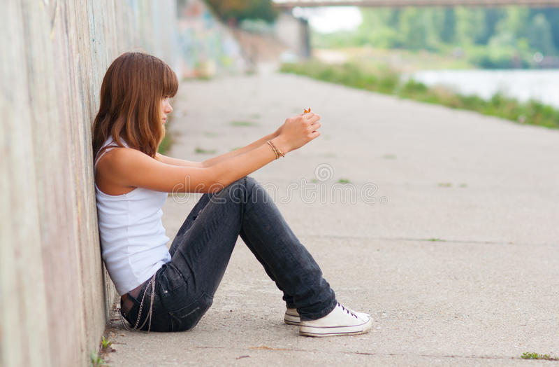 Den SAD tonårs- flickan som alone sitter i stads-, environmen royaltyfri foto