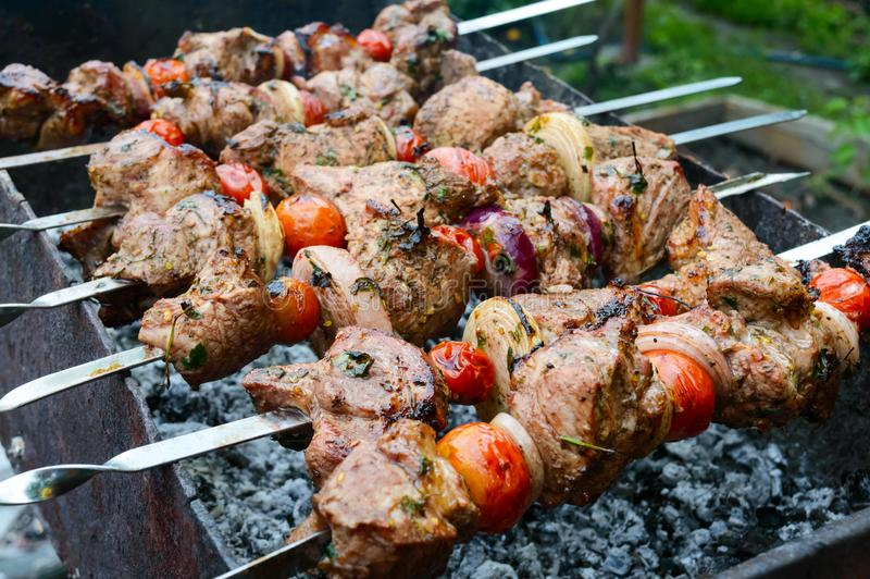 Den saftiga kebaben från griskött, tomater på steknålar, stekte på en utomhus- brand arkivbilder
