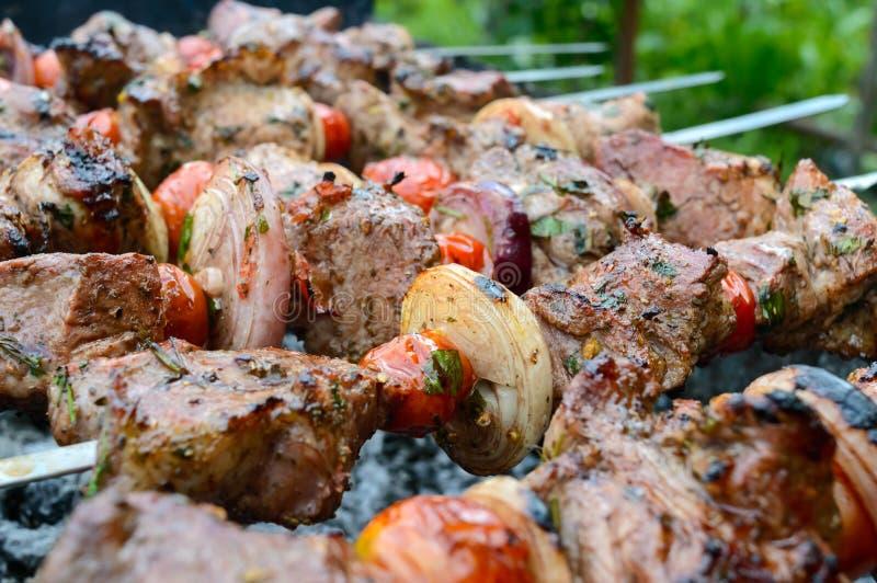 Den saftiga kebaben från griskött, tomater på steknålar, stekte på en utomhus- brand arkivfoto
