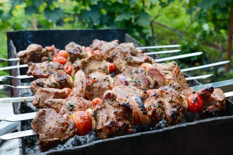 Den saftiga kebaben från griskött, tomater på steknålar, stekte på en utomhus- brand royaltyfri foto