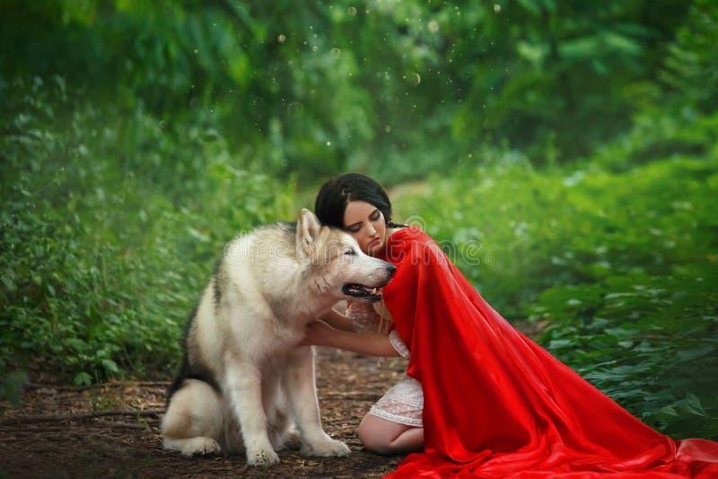 Den sagolika bilden, attraktiv dam för mörker-haired brunett i kort vit klänning, den långa röda scharlakansröda kappan som ligge royaltyfria bilder