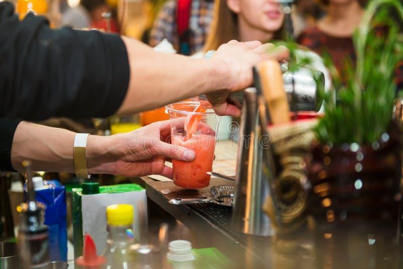Den sakkunniga pro-bartendern gör coctailen och den hällande drinken in i ett plast- exponeringsglas på färgbakgrunden med folk d fotografering för bildbyråer