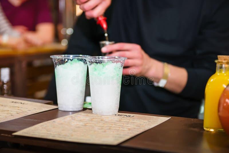 Den sakkunniga pro-bartendern gör coctailen och den hällande drinken in i ett plast- exponeringsglas på färgbakgrunden med folk d royaltyfria foton