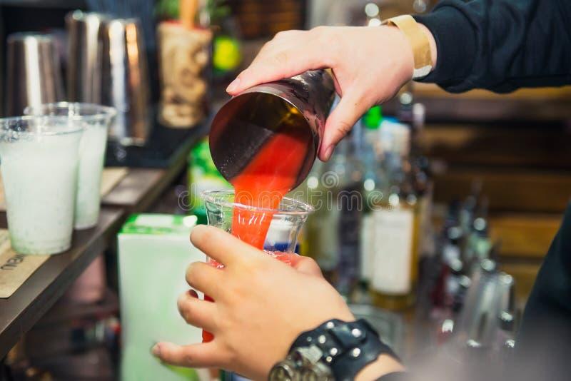 Den sakkunniga pro-bartendern gör coctailen och den hällande drinken in i ett plast- exponeringsglas på färgbakgrunden med folk d royaltyfri bild