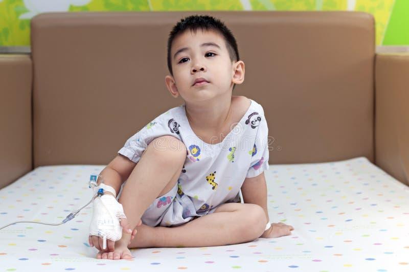 Den salthaltiga lösningen av patientbarnet sitter förestående på sängkänseln som borrar sund sjukvårdomsorg av sjukhuslivförsäkri royaltyfri foto