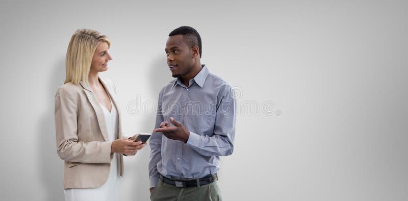Den sammansatta bilden av att le affärskvinnan och affärsmannen samtalar royaltyfria foton