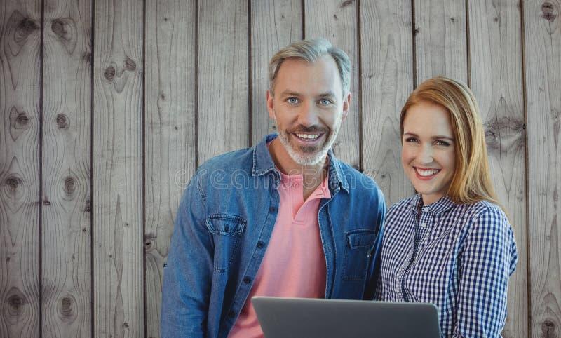 Den sammansatta bilden av att le affärsmannen och affärskvinnan rymmer en bärbar dator arkivbilder