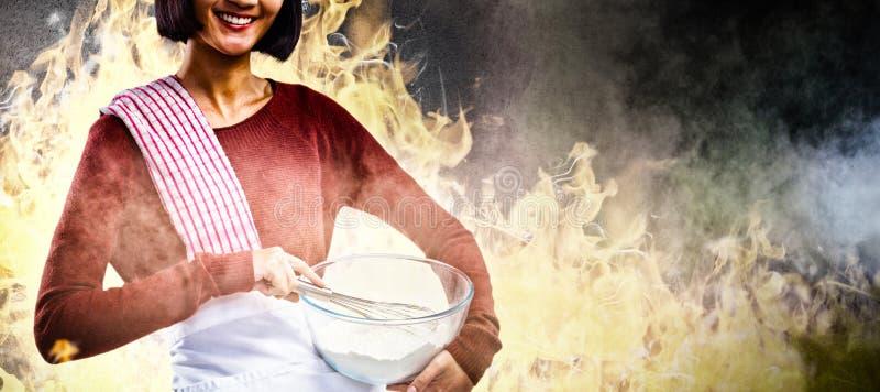 Den sammansatta bilden av att le blandande mjöl för den kvinnliga kocken i bunke med viftar fotografering för bildbyråer