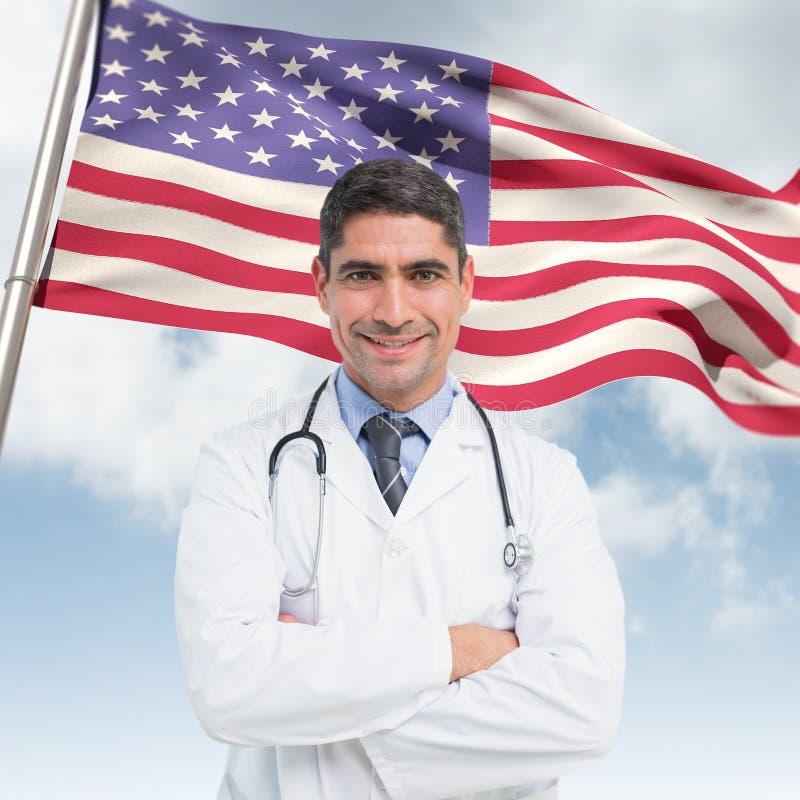 Den sammansatta bilden av att le den manliga doktorn med armar korsade i sjukhus fotografering för bildbyråer