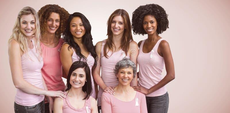 Den sammansatta bilden av att le kvinnor i rosa färger utrustar att posera för bröstcancermedvetenhet arkivbilder