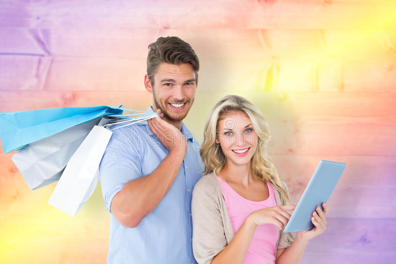 Den sammansatta bilden av attraktivt barn kopplar ihop hållande shoppingpåsar genom att använda minnestavlaPC royaltyfri fotografi