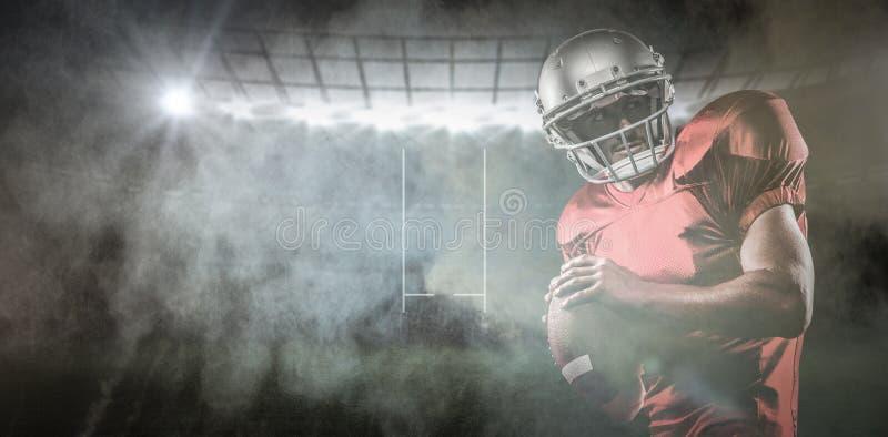 Den sammansatta bilden av den amerikanska fotbollsspelaren i den röda ärmlös tröja som ser bort, medan hållande, klumpa ihop sig arkivbild