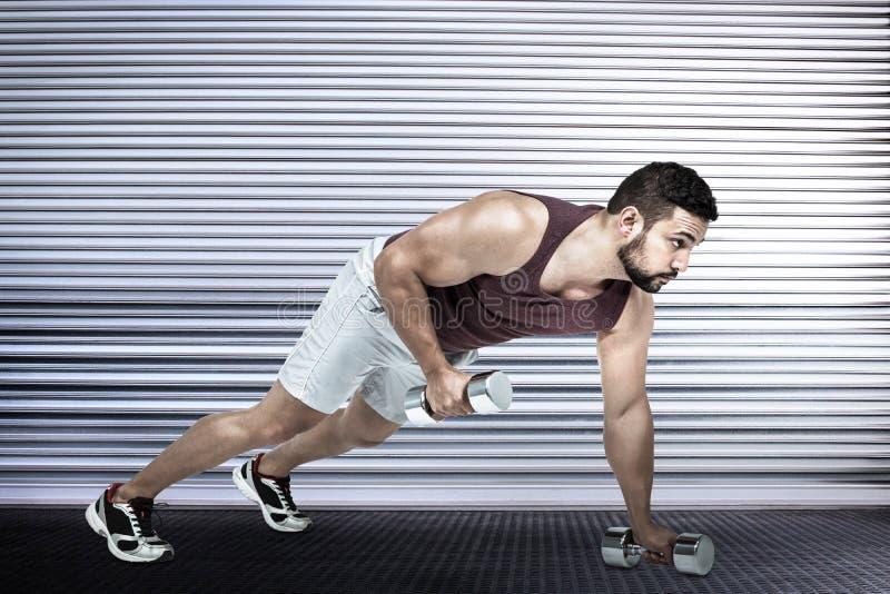 Den sammansatta bilden av den muskulösa mannen som att göra skjuter, ups med hantlar royaltyfri foto